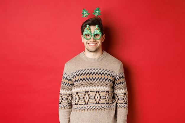 冬のセーターとパーティーグラスで幸せでかわいい男の肖像画、新年やクリスマスを祝って、赤い背景の上に立って笑っている