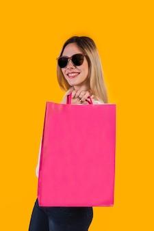 Портрет счастливой и позитивной белокурой девушки с розовой сумкой compa на желтом фоне.