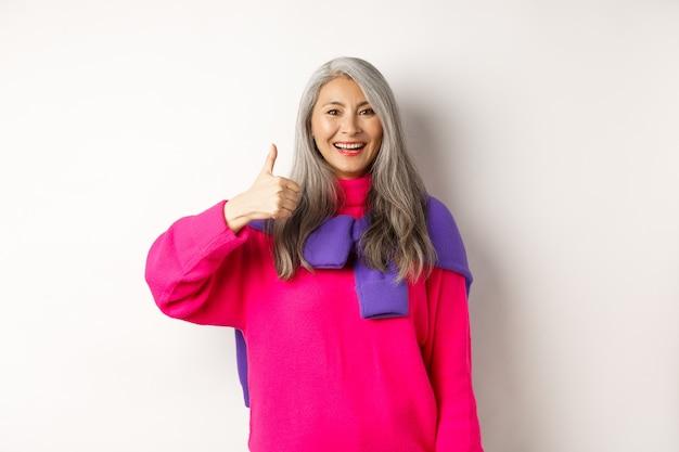 Портрет счастливой и удовлетворенной азиатской старшей женщины показывая большой палец вверх, одобрение и как что-то, усмехаясь и хваля продукт, стоя над белой предпосылкой.