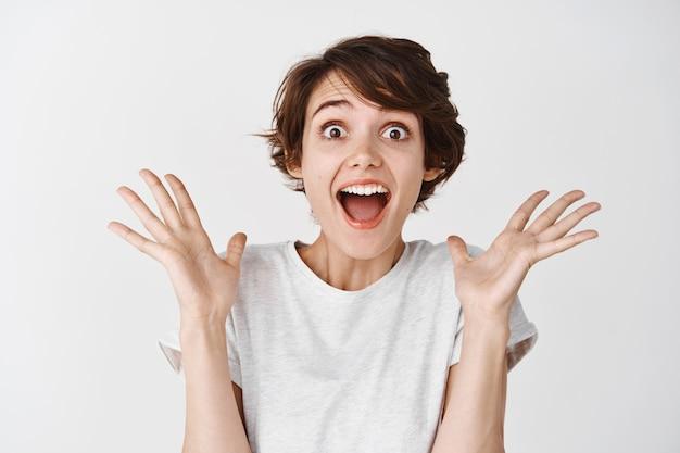 행복하고 놀란 여성의 초상화는 예라고 외치고, 놀란 손을 들고, 멋진 프로모션 거래를 확인하고, 흰 벽에 서 있습니다.
