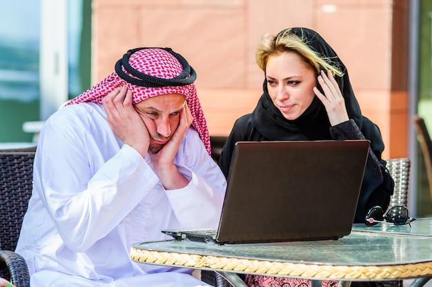 幸せなアラビア語の実業家と夏のトロピカルカフェで実業家の肖像画。フリーランスおよびリモートワーク。アラビア語の女性と恋にアラブ人のカップルが海岸で一緒に働く