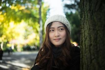 ツリーで幸せなアジアの美しい若い女性の肖像