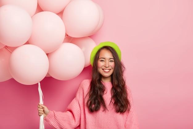행복 한 아시아 갈색 머리 아가씨의 초상화는 부드럽게 미소 짓고, 암탉 파티에 와서, 큰 무리의 풍선을 들고, 녹색 베레모와 대형 스웨터를 입습니다.