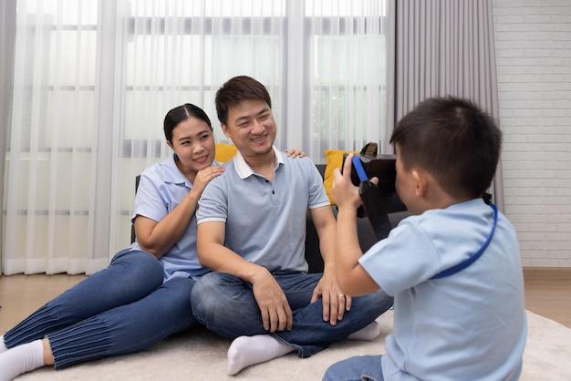 Портрет счастливой азиатской пары фотографирует сына в гостиной дома