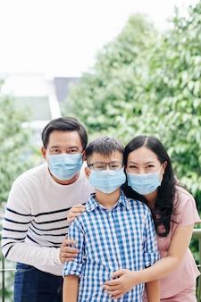 屋外に立っているときに抱き締める医療マスクで幸せなアジアの家族の肖像画