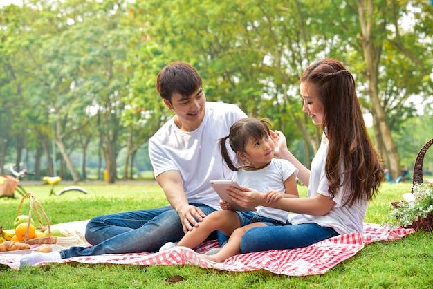 피크닉 식사와 함께 행복 한 아시아 가족의 초상화