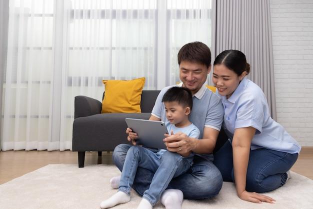 Портрет счастливой азиатской семьи с сыном с помощью планшета в гостиной дома