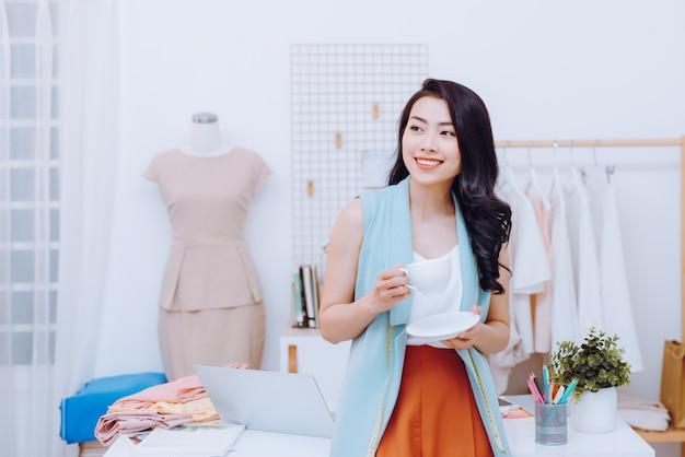Портрет счастливой азиатской коммерсантки модельера на студии. улыбается, стоит, смотрит в камеру.