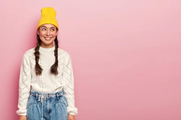 행복 한 아시아 여자의 초상화는 기꺼이 옆으로 보이고, 노란 모자, 흰색 스웨터와 청바지를 입은 즐거운 미소를 가지고 있으며, 루즈 뺨과 메이크업을 가지고 있으며, 장미 빛 벽 위에 포즈를 취합니다.