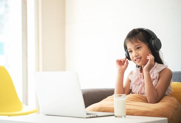 自宅で先生とオンラインで勉強するためにビデオ電話会議を使用して幸せなアジアの女の子の肖像画。