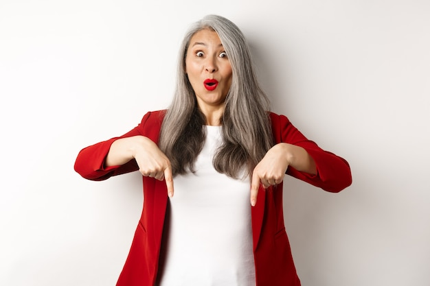 로고를 보여주는 빨간 재킷에 행복 아시아 여자의 초상화, 아래로 손가락을 가리키고 쾌활한 미소, 제스처, 흰색 배경을 확인하십시오.