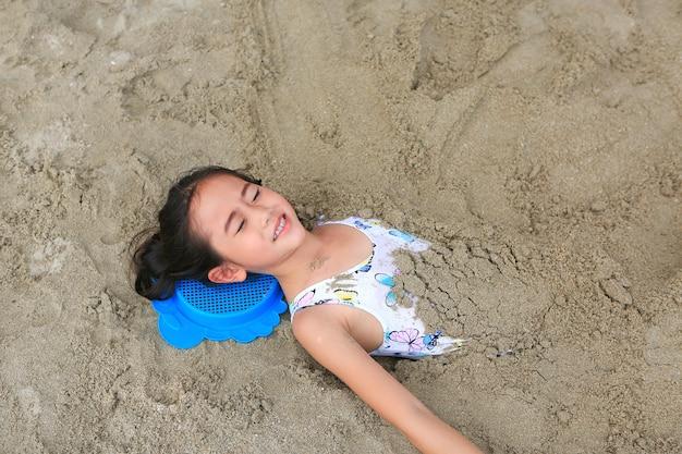Портрет счастливой азиатской маленькой девочки похоронили в песке на пляже