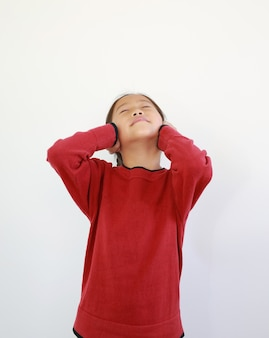耳に手を置く幸せなアジアの小さな子供の肖像画。うれしそうな子供は目を閉じて、白い孤立した背景に笑みを浮かべて
