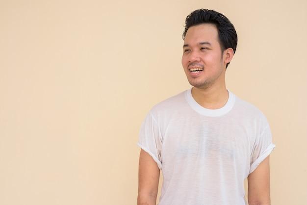 생각하는 동안 야외에서 평범한 배경에 흰색 티셔츠를 입은 행복한 아시아 남자의 초상화