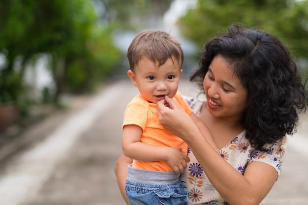 幸せなアジアの母親と屋外で一緒に結合する多民族の赤ちゃんの息子の肖像画