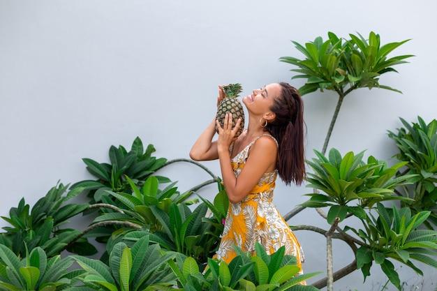 黄色の夏のドレスで幸せなアジアの笑顔の女性の肖像画はパイナップルを保持します