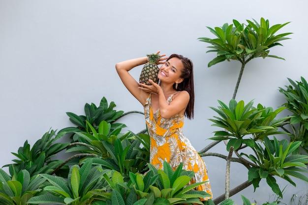 노란색 여름 드레스에 행복 한 아시아 웃는 여자의 초상화 잡고 파인애플