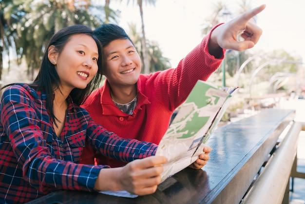 Портрет счастливой пары азиатских путешественников держа карту и ищущих направления. концепция путешествий и отдыха.