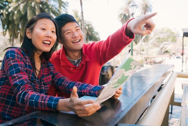 地図を持って道順を探している幸せなアジアの旅行者カップルの肖像画。旅行と休日のコンセプト。