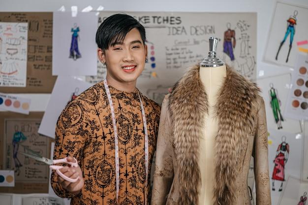행복 한 아시아 젊은 남성 재단사의 목에 테이프를 측정 하 고 패션 스튜디오에서 카메라를 보고.