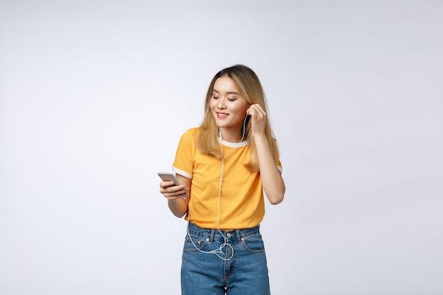 幸せなアジアの若い女性の肖像画はヘッドフォンで音楽を聴く