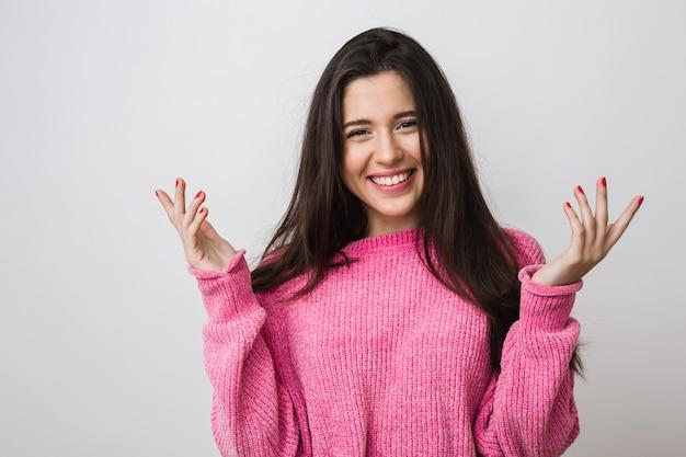 暖かいピンクのセーター、長い髪、自然な表情、誠実な笑顔、前向きな気分、手をつないで、驚いて、分離された幸せな魅力的な女性の肖像画