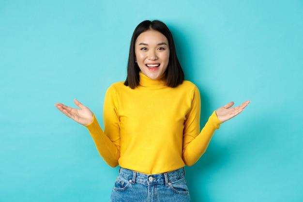 Портрет счастливой привлекательной женщины, раскинувшей руки в сторону и улыбающейся, удивленной видеть вас, стоящей на синем фоне