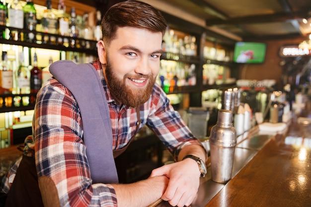 Портрет счастливого привлекательного молодого бармена с шейкером в пабе