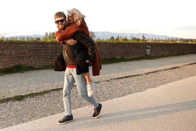 疲れている、一人で歩くことができない彼の美しいガールフレンドにピギーバックライドを与えるために広く喜んで笑っている色合いの幸せな魅力的な若いひげを生やした男の肖像画。人、愛、人間関係