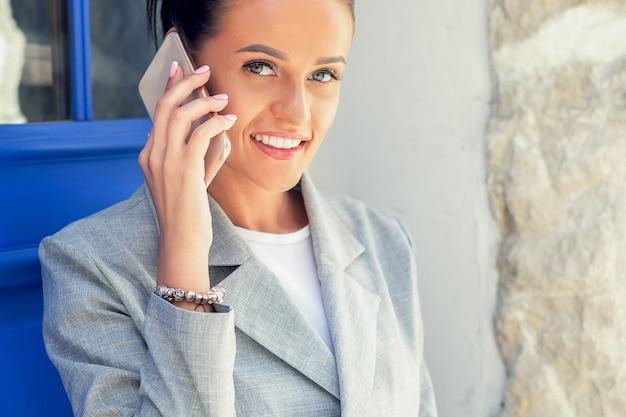 Портрет счастливой привлекательной молодой коммерсантки разговаривает на умном телефоне возле двери на открытом воздухе.
