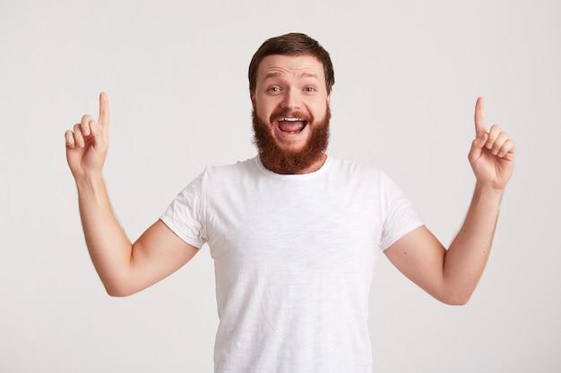 ひげを生やした幸せな魅力的な若い男のヒップスターの肖像画はtシャツを着て自信を持って見え、白い壁に指を隔離してコピースペースの側を指しています