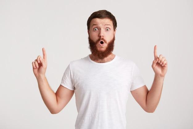 Портрет счастливого привлекательного молодого человека-хипстера с бородой в футболке выглядит уверенно и указывает в сторону на copyspace с пальцем, изолированным над белой стеной
