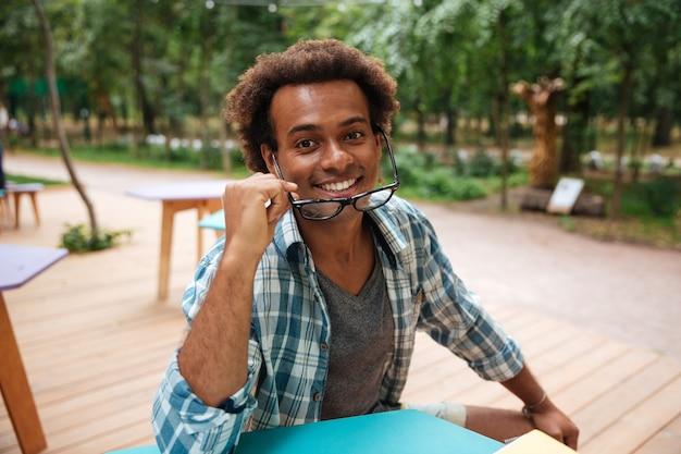 Портрет счастливого привлекательного молодого человека в очках, сидящего на открытом воздухе