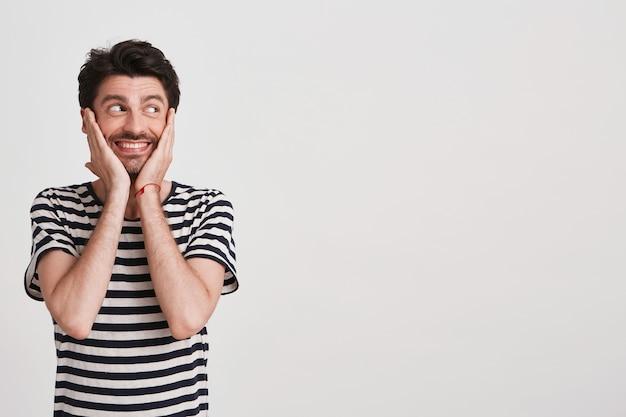 Портрет счастливого привлекательного молодого человека с щетиной в полосатой футболке чувствует себя взволнованным и улыбающимся изолированным на белом