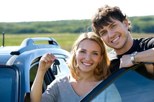 車の近くに立っている鍵を示す幸せな美しいカップルの肖像画