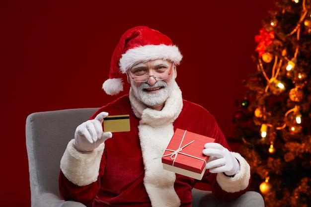Портрет счастливого бородатого санта-клауса с кредитной картой и подарочной коробкой в руках, он покупает рождественские подарки онлайн