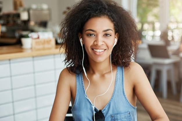 Портрет счастливой красивой африканской женщины в наушниках усмехаясь сидеть в кафе.
