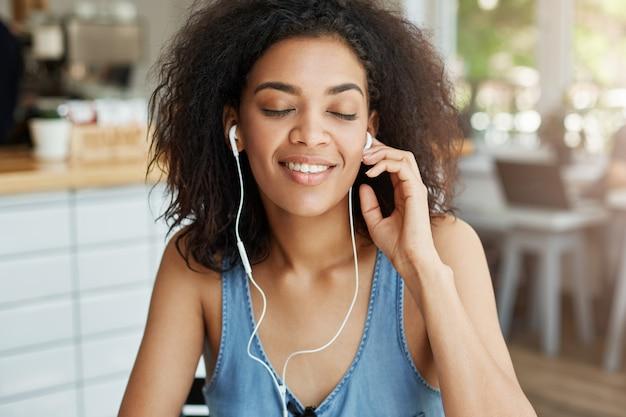 카페에 앉아 웃 고 헤드폰에서 음악을 듣고 행복 한 아름 다운 아프리카 여자의 초상화. 감긴 눈.
