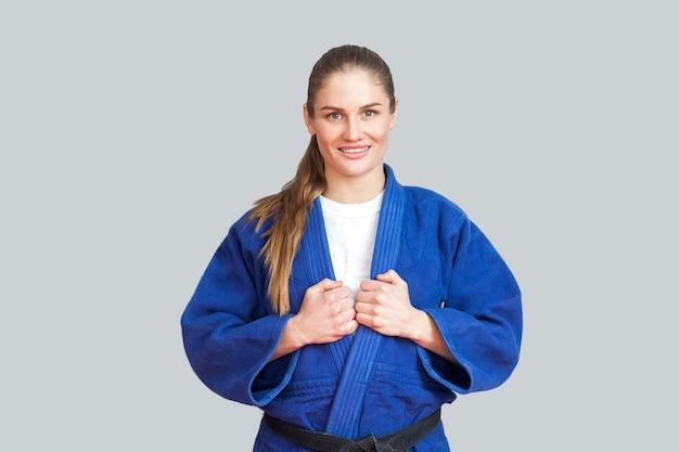 黒帯が立って、歯を見せる笑顔でカメラを見ている青い着物で幸せな美しい運動空手女性の肖像画。日本の武道の概念。屋内、スタジオショット、灰色の背景
