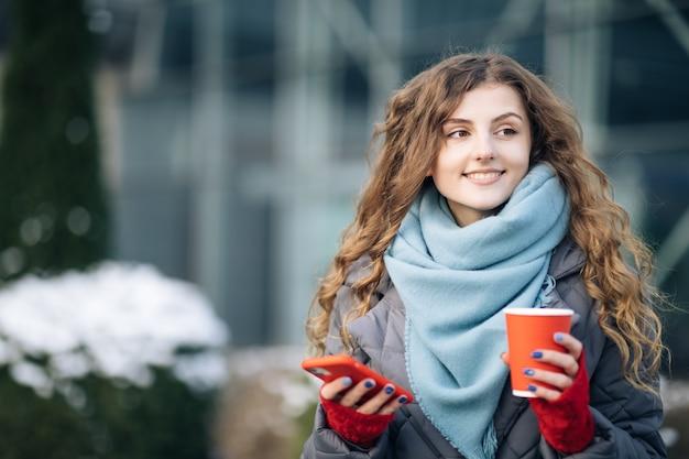 커피 컵 테이크 아웃으로 행복 한 아름 다운 곱슬 여자의 초상화는 휴대 전화 문자 메시지를 사용합니다.