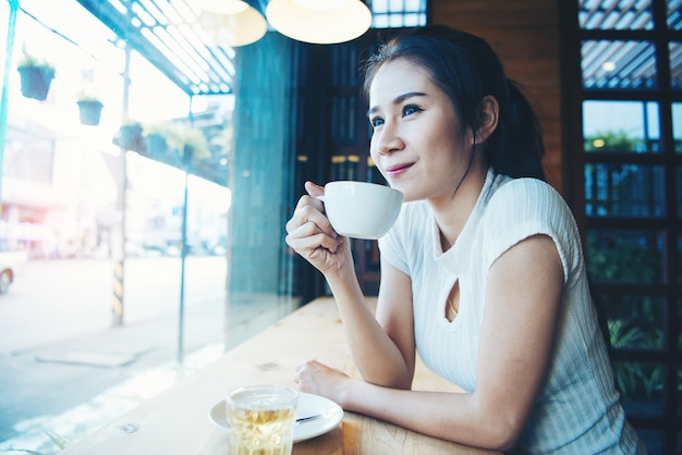 手でマグカップと幸せな美しい女性の肖像画