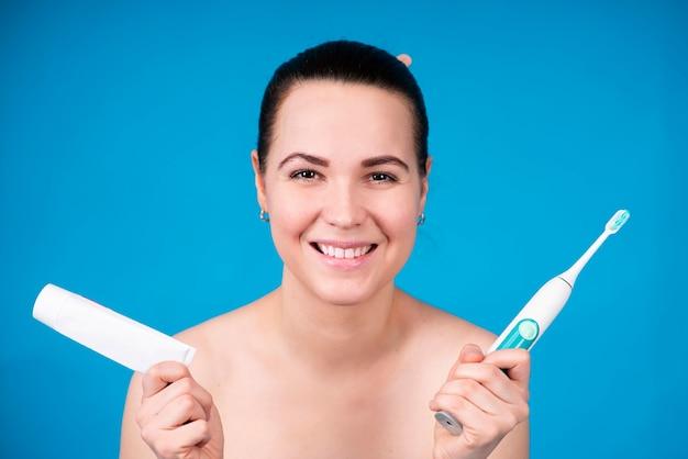 Портрет счастливой красивой девушки, молодой женщины, улыбающейся и показывающей свои белые зубы, держащей электро