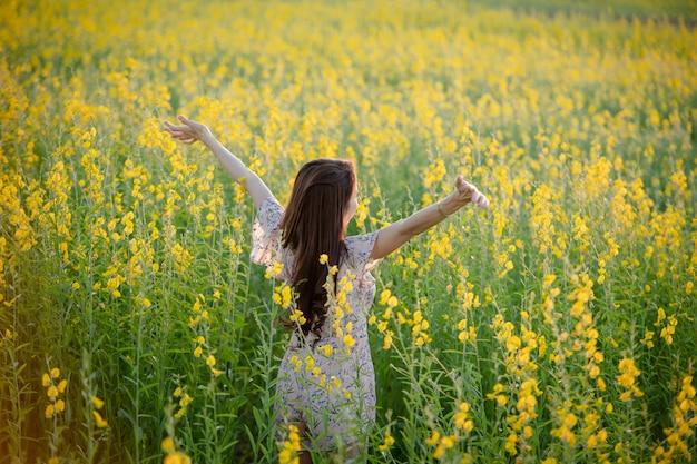 공원에서 편안한 행복 아름 다운 행복 한 젊은 여자의 초상화. 노란색 꽃 정원에서 여자입니다.