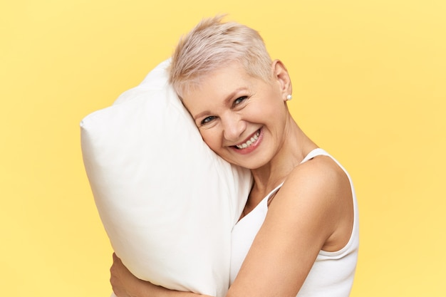Портрет счастливой красивой женщины средних лет с волосами рубашки, имеющими энергичный вид из-за полноценного ночного сна на удобной белой подушке из пены с эффектом памяти.