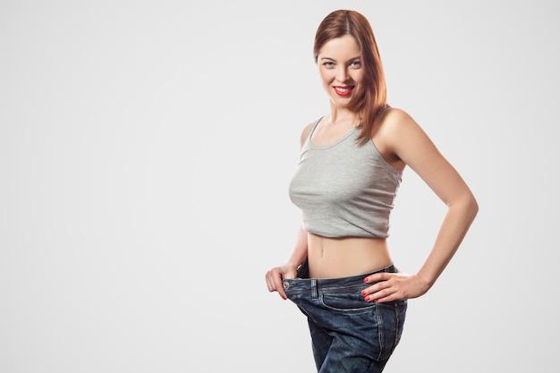 큰 청바지와 회색 상의를 입은 젊은 여성의 행복한 아름다운 날씬한 허리의 초상화는 성공적인 체중 감량, 실내, 스튜디오 촬영, 밝은 회색 배경, 다이어트 개념에 격리되어 있습니다.