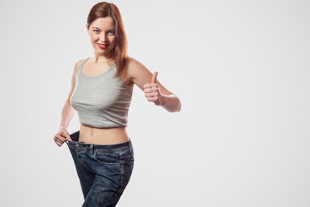 큰 청바지와 회색 상의를 입고 성공적인 체중 감량, 실내, 스튜디오 촬영, 밝은 회색 배경, 다이어트 개념에 격리된 젊은 여성의 행복하고 날씬한 허리 초상화.
