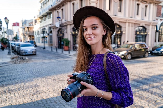 Портрет счастливого красивого стильного фотографа женщины в шляпе с цифровой камерой dslr, делающей фотографии, идя по европейскому городу