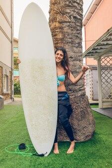 ヤシの木の前でサーフボードを保持しているビキニとウェットスーツと幸せな美しいサーファーの女性の肖像画