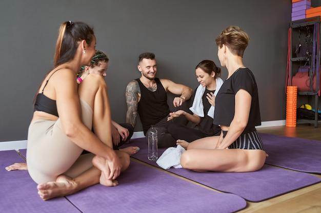 피트니스 요가 수업에서 대화를 나누는 동안 보라색 매트에 앉아 행복 아름다운 팀의 초상화
