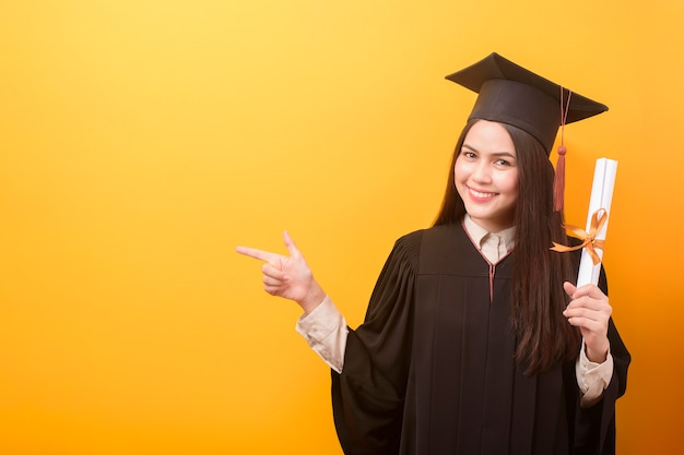 Портрет счастливой красивая женщина в выпускной платье держит свидетельство об образовании на желтом фоне